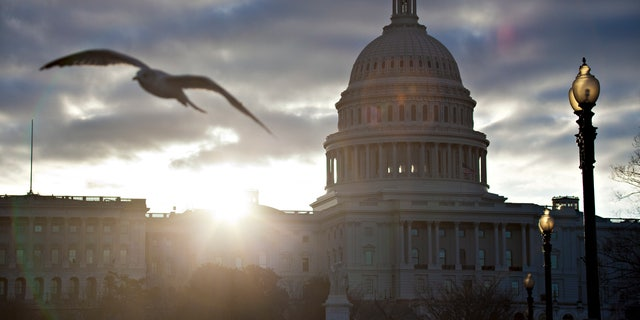 FILE -- At dawn, the sun breaks through dark clouds over Capitol Hill in Washington.