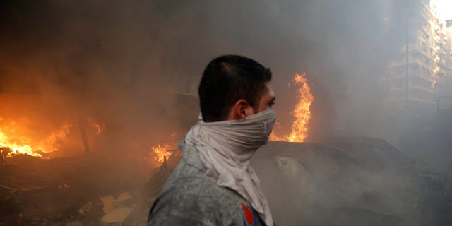 A Hezbollah civil defense worker walks past a burned car at a car bomb in the southern suburb of Beirut, Lebanon, Thursday, Aug. 15, 2013.
