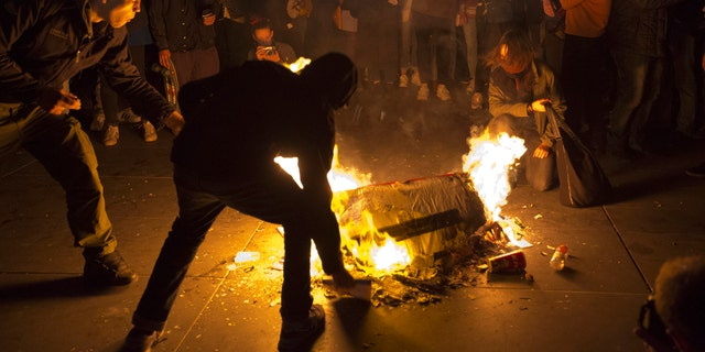 People burn litter as they protest in Paris, Sunday, April 23, 2017.