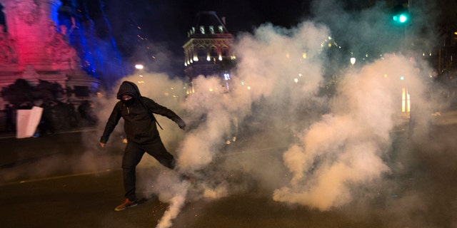 A demonstrator runs away from tear gas during clashes with police in Paris, Sunday, April 23, 2017. Protesters are angry that far-right leader Marine Le Pen is advancing in the French presidential runoff.