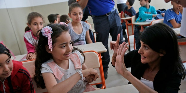 In this May 24 photo, U.S. Ambassador to the U.N. Nikki Haley, right, talks with Syrian refugee children at the Sakirpasa Umran school, funded by the US government, following its opening ceremony in Adana, southern Turkey.
