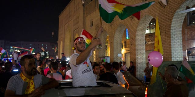 A man waves the Kurdish flag in the streets of Irbil after polling stations closed on Monday, Sept. 25, 2017. The Kurds of Iraq were voting in a referendum on support for independence.