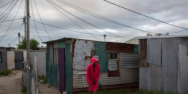 In this Feb. 2, 2018 photo, a woman collects water in a settlement near South Africa's drought-hit city of Cape Town. About a quarter of Cape Town's population lives in the informal settlements, where they get water from communal taps instead of individual taps at home like in the richer suburbs.