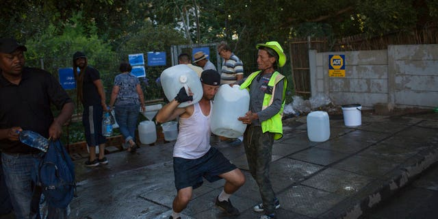 "Two men help each other carry water at a source for natural spring water in Cape Town. Cape Town residents are allowed to use no more than 50 liters of water daily. Authorities say they might have to turn off most city taps in May if residents don't save enough water in what they call ""Day Zero."""