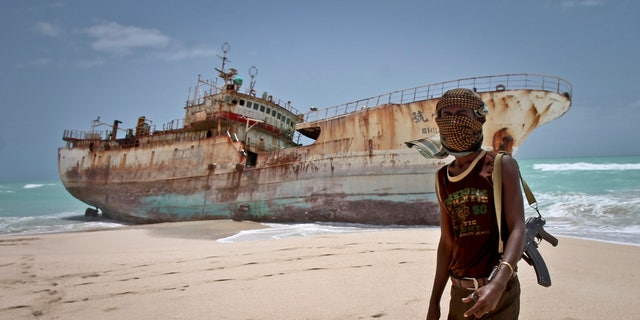 In this photo taken Sunday, Sept. 23, 2012, a masked Somali pirate stands near a Taiwanese fishing vessel that washed up on shore after the pirates were paid a ransom and released the crew, in the once-bustling pirate den of Hobyo, Somalia. Pirates have increasingly turned toward kidnapping because it yields a higher return than selling stolen goods.