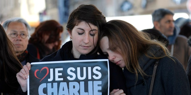 """People pay tribute to the victims of the satirical newspaper """"Charlie Hebdo"""", in Marseille, southern France, Thursday, Jan. 8, 2015, a day after masked gunmen stormed the offices of a satirical newspaper and killed 12 people. French police hunted Thursday for two heavily armed men — one with a terrorism conviction and a history in jihadi networks — in the methodical killing of 12 people at a satirical newspaper that caricatured the Prophet Muhammad. Placard reads """"I am Charlie"""" . (AP Photo/Claude Paris)"""