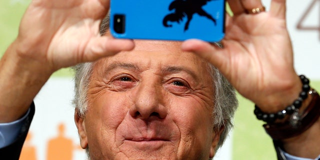 """April 9, 2013: Actor Dustin Hoffman takes a photograph during a press conference to promote his film """"Quartet"""" in Tokyo."""