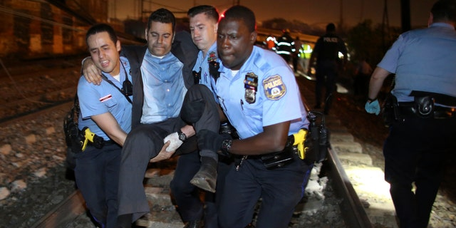 Emergency personnel help a passenger at the scene of the train wreck