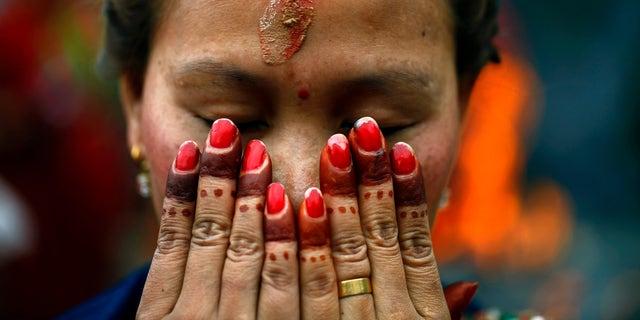 A Nepalese Hindu woman offers prayers at the Pashupatinath temple during Teej festival celebrations in Katmandu, Nepal, Tuesday, Sept. 18, 2012. (AP Photo/Niranjan Shrestha)