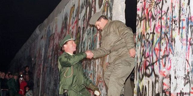 A West German policeman, left, helps an East German border guard who climbs through a gap of the Berlin Wall in 1989.