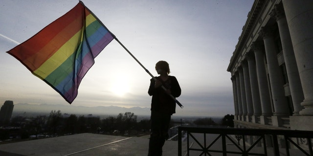 Corbin Aoyagi, a supporters of gay marriage, waves his flag during a rally at the Utah State Capitol.