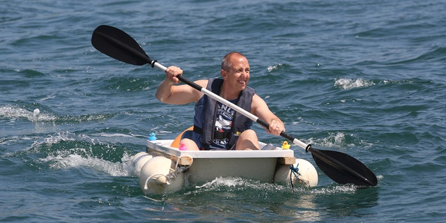 Plumber Iain Bevan, 51, rows across seas at Torbay inside a bath tub to raise money for charity.