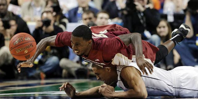 Florida State's Okaro White, top, falls over Virginia's Malcolm Brogdon, bottom, as they chase a loose ball during the second half of an NCAA college basketball game in the quarterfinal round of the Atlantic Coast Conference tournament in Greensboro, N.C., Friday, March 14, 2014. (AP Photo/Gerry Broome)