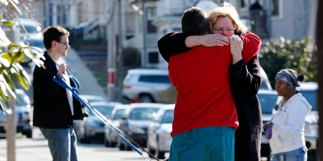 Neighbors hug outside the home of the Richard family in the Dorchester neighborhood of Boston, Tuesday, April 16, 2013.  Martin Richard, 8, was killed in Monday's bombing at the finish line of the Boston Marathon.