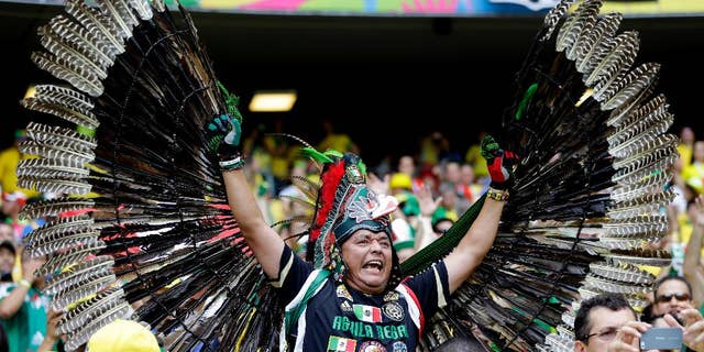 A Mexican fan shows off his costume before the group A World Cup soccer match between Brazil and Mexico at the Arena Castelao in Fortaleza, Brazil, Tuesday, June 17, 2014. (AP Photo/Andre Penner)