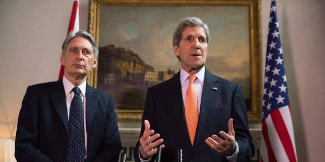 """Britain's Foreign Secretary Philip Hammond and U.S. Secretary of State John Kerry, right, deliver a statement at a press conference in London, Saturday Feb, 21, 2015.  US Secretary of State John Kerry, in London for talks with Foreign Secretary Philip Hammond, said Russia's conduct was """"simply unacceptable"""" and that he expected to see agreement on further international sanctions in the coming days. """"Russia has engaged in an absolutely brazen and cynical process over these last days. We know to a certainty what Russia has been providing to the separatists, how Russia is involved with the separatists,"""" he told reporters. (AP Phto/Neil Hall/Pool)"""