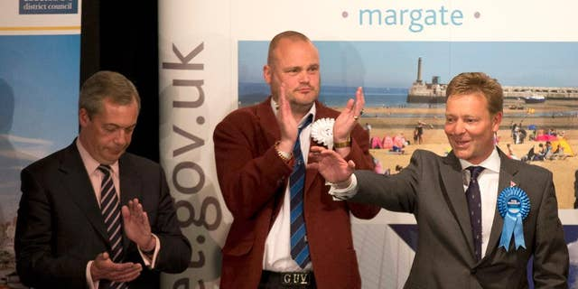 """The Conservative Party's Craig Mackinlay, right, waves after winning the count for the South Thanet seat beside, from left,  Nigel Farage the leader of the UK Independence Party (UKIP) and Al Murray a comedian who performs as """"The Pub Landlord"""" at the Winter Gardens in Margate, south east England, Friday, May 8, 2015. British Prime Minister David Cameron appeared poised to remain in power Friday, with early British election results and exit polls indicating his Conservatives had won a resounding victory and will return to 10 Downing Street in a stronger position than before. (AP Photo/Matt Dunham)"""