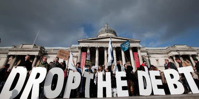 """Protesters hold placards during a rally to show solidarity with Greece in central London, Sunday, Feb. 15, 2015. Hundreds of protesters gathered in support of the new government and the anti-austerity movement in Greece. Greece's new left-wing government is pressing for a short-term """"bridge"""" agreement with eurozone lenders and a longer-term debt relief deal later this year. (AP Photo/Lefteris Pitarakis)"""