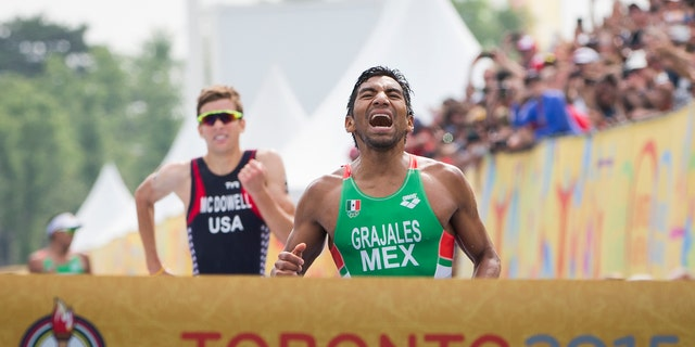 Mexico's Crisanto Grajales, right, reacts before crossing the finish line to win the gold medal ahead of United States' Kevin McDowell during the Men's Triathlon at the Pan Am Games in Toronto, Ontario, Sunday, July 12, 2015. (AP Photo/Felipe Dana)