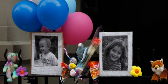 Photographs of the two children allegedly stabbed by their nanny are displayed alongside balloons and stuffed animals at a memorial outside the apartment building were they lived in New York.