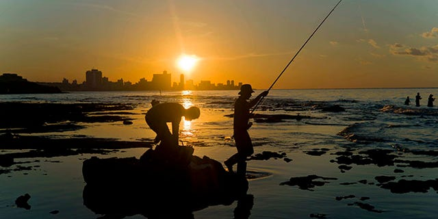 In this Nov. 11, 2016 photo, fishermen throw their fishing rods from Chivo beach as the sun sets in Havana, Cuba. Cuba has been renowned for its fishing at least since the days of Ernest Hemingway, and foreigners by the thousands come each year to fish in waters largely protected by Cubaâs lack of development. (AP Photo/Ramon Espinosa)