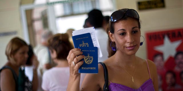 A woman shows her passport and that of her son to reporters as she leaves an immigration office in Havana, Cuba, Tuesday, Oct 16, 2012.