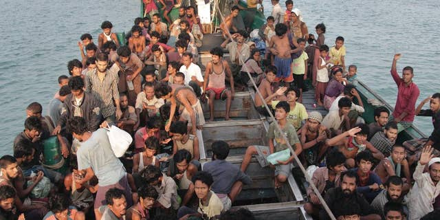 Migrants wait to be be rescued by Acehnese fishermen on their boat on the sea off East Aceh, Indonesia, Wednesday, May 20, 2015. In a potential breakthrough in Southeast Asia's humanitarian crisis, Indonesia and Malaysia offered Wednesday to provide temporary shelter to thousands of migrants stranded at sea after weeks of saying they weren't welcome. But they appealed for international help, saying the crisis was a global, not a regional, problem. (AP Photo/S. Yulinnas)