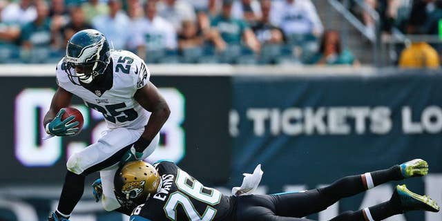 Philadelphia Eagles' LeSean McCoy, left, tries to break a tackle by Jacksonville Jaguars' Josh Evans during the first half of an NFL football game, Sunday, Sept. 7, 2014, in Philadelphia. (AP Photo/Matt Rourke)