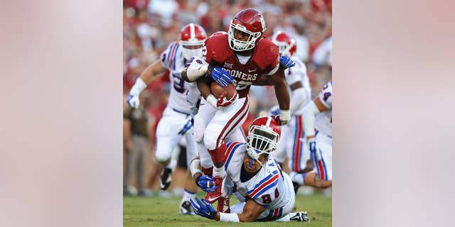 Oklahoma running back Samaje Perine (32) escapes a tackle attempt by Louisiana Tech defensive lineman Andre Taylor during the second quarter of an NCAA college football game in Norman, Okla., Saturday, Aug. 30, 2014. (AP Photo/Sue Ogrocki)