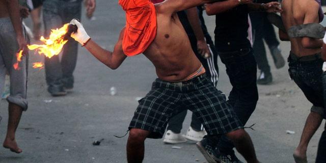 Oct. 3, 2012 - A Bahraini anti-government protester throws a petrol bomb toward riot police, unseen, firing tear gas and stun grenades in Sadad, Bahrain.