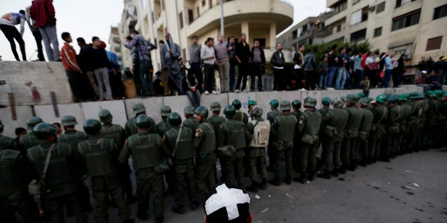 Dec. 9, 2012 - Egyptian army soldiers stand guard as protesters stand on top of cement blocks near the presidential palace in Cairo, Egypt.