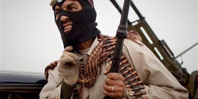 March 18: A Libyan rebel grimaces on the frontline near Sultan, south of Benghazi. (AP)