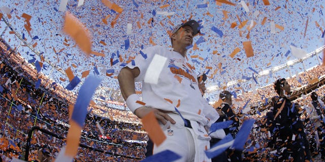 January 19, 2014: Denver Broncos quarterback Peyton Manning is engulfed in confetti during the trophy ceremony after the AFC Championship NFL playoff football game in Denver. The Broncos defeated the Patriots 26-16 to advance to the Super Bowl. (AP Photo/Charlie Riedel)