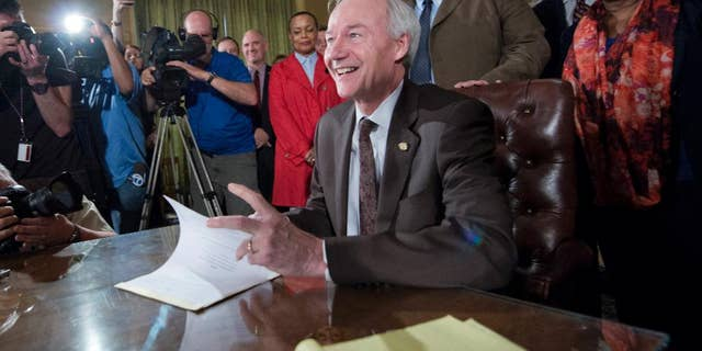 Arkansas Gov. Asa Hutchinson signs a reworked religious freedom bill into law after it passed in the House at the Arkansas state Capitol in Little Rock, Ark., Thursday, April 2, 2015. Lawmakers in Arkansas and Indiana passed legislation Thursday that they hoped would quiet the national uproar over new religious objections laws that opponents say are designed to offer a legal defense for anti-gay discrimination. (AP Photo/Brian Chilson)