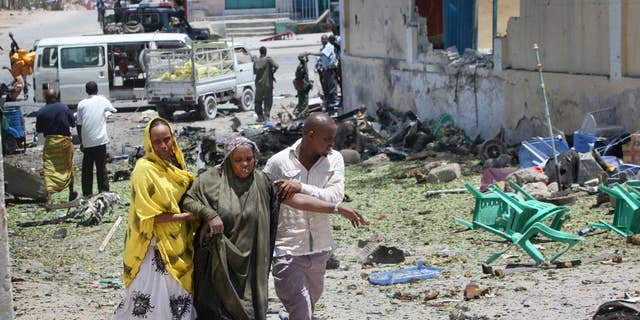 More than thirty people in Minnesota have been charged in recent years with conspiring to join terrorist groups such as ISIS and al-Shabab in Somalia. Here, people assist the wounded after an attack in Mogadishu, Somalia.