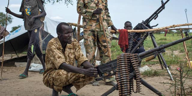 Rebel soldiers guard the village of Majieng, about 6km from the town of Bentiu, in South Sudan Saturday, Sept. 20, 2014. Seyoum Mesfin, the chairman of the South Sudan mediation process said Saturday there is renewed fighting in South Sudan between government and rebel troops and that it is a purposeful act aimed at derailing the next phase of the peace process. (AP Photo/Matthew Abbott)