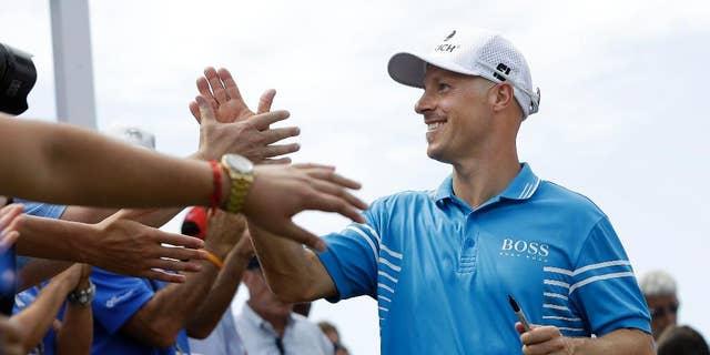 Ben Crane is congratulated after winning the St. Jude Classic golf tournament Sunday, June 8, 2014, in Memphis, Tenn. Crane won the tournament with a score of 10-under 270.(AP Photo/Mark Humphrey)
