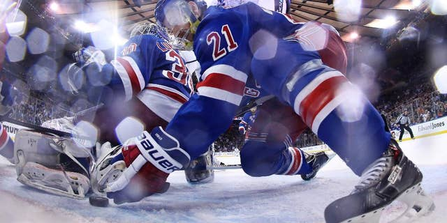 New York Rangers center Derek Stepan (21) reaches to move the puck away from the goal behind goalie Henrik Lundqvist (30) in the third period during Game 4 of the NHL hockey Stanley Cup Final, Wednesday, June 11, 2014, in New York. The Rangers won the game 2-1. (AP Photo/Bruce Bennett, Pool)