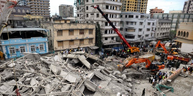 March 29, 2013 - Rescuers using mechanical diggers remove rubble from the site of a collapsed building in downtown Dar es Salaam, Tanzania.