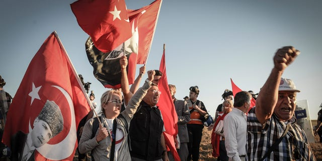 Aug. 5, 2013 - People hold national flags as they shout slogans outside the Silivri jail complex in Silivri, Turkey. Some 250 people - including military officers, politicians and journalists - received verdicts in a landmark and divisive trial in Turkey over an alleged conspiracy to overthrow Prime Minister Recep Tayyip Erdogan's government. Security forces set up barricades around the courthouse in Silivri to tighten security after supporters of defendants announced a demonstration against the five-year trial.