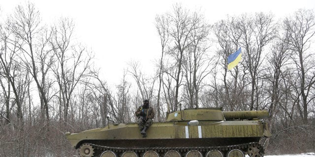 Feb. 16, 2015: An Ukrainian soldier rests on his vehicle near the road between the towns of Debaltseve and Artemivsk. (AP Photo/Petr David Josek)