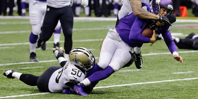 Minnesota Vikings quarterback Matt Cassel (16) is tackled by New Orleans Saints middle linebacker Curtis Lofton (50) and strong safety Kenny Vaccaro (32) in the first half of an NFL football game in New Orleans, Sunday, Sept. 21, 2014. Cassel injured his foot injury on the play. (AP Photo/Bill Haber)
