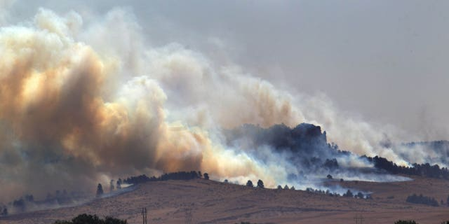 In this Saturday, Sept. 1, 2012 photo, smoke plumes rise from the West Ash Creek wildfire near Crawford Neb. The blaze is one of three wildfires burning in Nebraska and South Dakota, started earlier in the week by lightning. (AP Photo/Omaha World-Herald, Mark Davis) MAGS OUT; ALL NEBRASKA LOCAL BROADCAST TV OUT