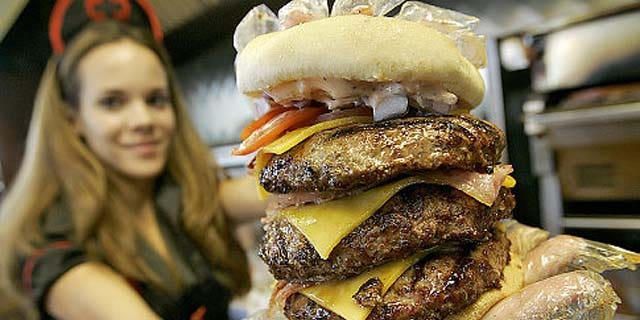 Courtney Chapman, a waitress dressed as a nurse at the Heart Attack Grill, holds up a triple bypass burger Friday, Dec. 1, 2006 in Tempe, Ariz.