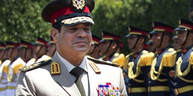 """April 24, 2013: In this file photo, Egyptian Defense Minister Gen. Abdel-Fattah el-Sissi reviews honor guards during an arrival ceremony for his U.S. counterpart at the Ministry of Defense in Cairo. Egypt's military chief says he """"can't turn his back"""" if the majority of Egyptians want him to run for president."""
