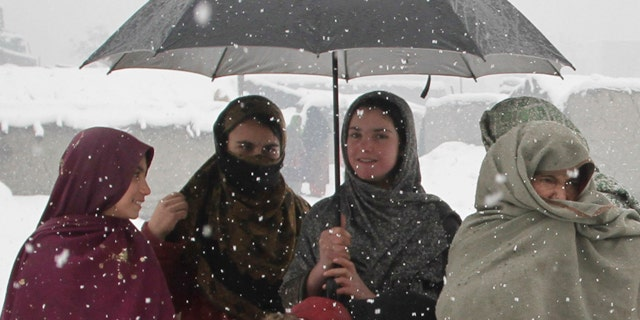 Feb. 20: Afghan refugee women wait with their children to receive donations at a refugee camp in Kabul.