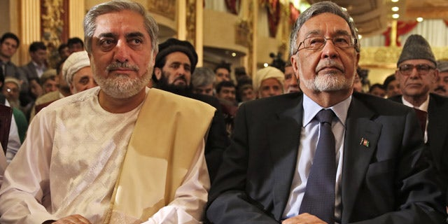 May 11, 2014: Afghan presidential candidate Abdullah Abdullah, left, and Afghan presidential candidate Zalmai Rassoul, right, listen during a news conference in Kabul, Afghanistan. (AP Photo/Massoud Hossaini)