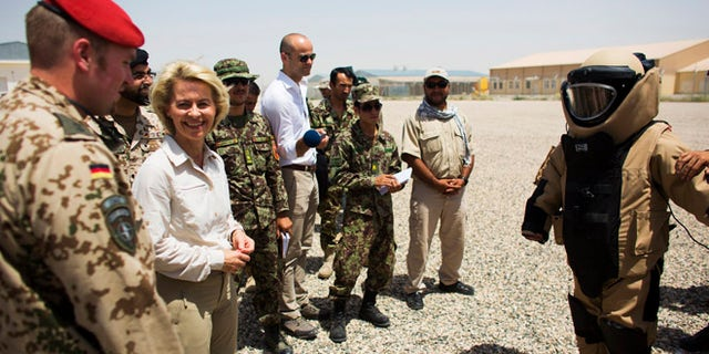 July 23, 2014: German Defence Minister Ursula von der Leyen, second left, stands next to an Afghan soldier wearing a bomb suit, right, during a demonstration at a sapper training facility at Camp Shaheen outside Mazar-i-Sharif, Afghanistan. (AP)