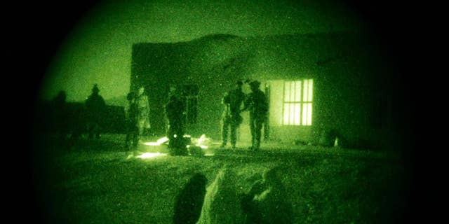 FILE - In this Oct. 28, 2009 file photo taken with a night vision scope, Afghan women and their children wait as U.S. Special Operations forces and Afghan National Army soldiers search their home during a joint operation targeting insurgents operating in Afghanistan's Farah province. Afghan President Ashraf Ghani has ordered a top-to-bottom review of the practices of the country's defense forces, including discussing a possible resumption of controversial night raids banned by his predecessor, The Associated Press has learned. The move appears aimed at revamping the military for the fight against the Taliban amid new indications that U.S. and international forces will play a greater role than initially envisaged.  (AP Photo/Maya Alleruzzo, File)