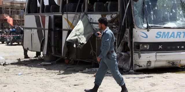 May 4, 2015 - An Afghan security man inspects the site of a suicide attack in Kabul, Afghanistan. An Afghan official says a suicide bomber struck a minibus carrying government employees in Kabul, killing at least one person and wounding more than a dozen.